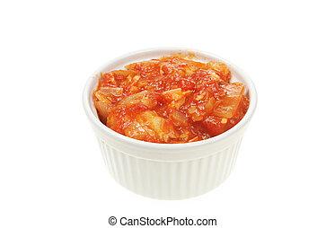 Tomato chutney in a ramekin isolated on white