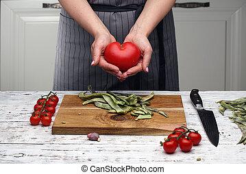 tomato., contre, blanc, cuisinier, kitchen., tablier, prise, femme, love., mains, nourriture., concept., black-striped, gris, santé, tomate, sain, forme coeur, amour, cuisine