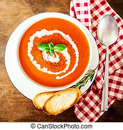 Tomato cream soup with croutons and spoon in a white bowl on rustic wooden kitchen table. Top view