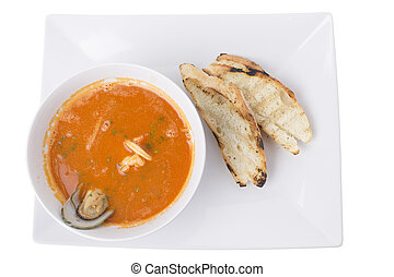 Tomato cream soup with seafood and croutons.