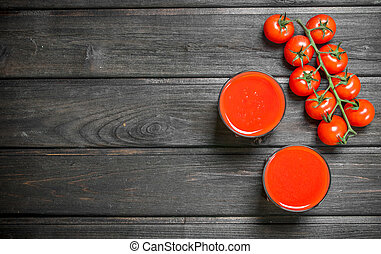 Tomato juice in a glass and a branch of ripe tomatoes.