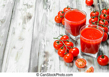 Tomato juice in a glass and fresh tomatoes on a branch.
