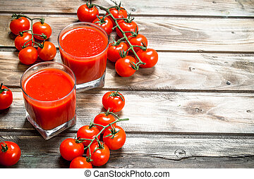 Tomato juice in a glass and ripe tomatoes on a branch.