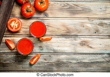 Tomato juice in a glass and tomato slices.
