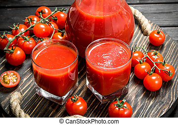 Tomato juice in a glass on tray and ripe tomatoes.