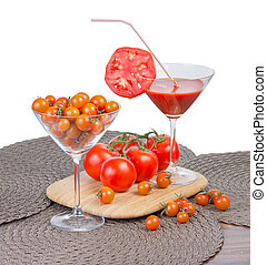 Tomato juice in the glass, orange cherry tomatoes and red tomatoes on vine isolated on white background .