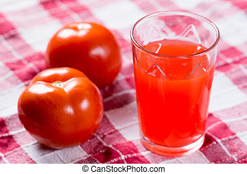 Tomato juice in the glass with fresh tomatos