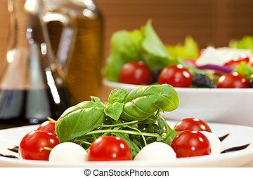 Tomato, mozarella, rocket or rocquet salad with olive oil and balsamic vinegar dressing and basil garnish shot in golden sunshine
