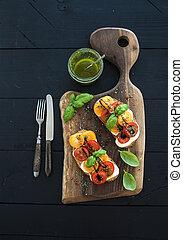 Tomato, mozzarella and basil sandwiches on dark wooden chopping board, pesto jar, dinnerware over black background, top view