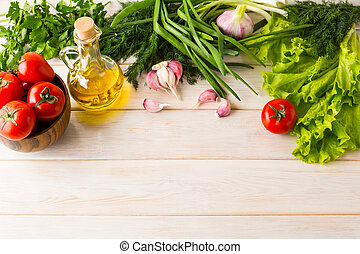 Tomato, olive oil, and garlic on white wooden background