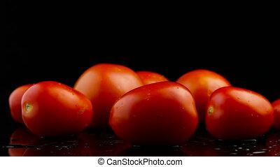 Tomato on black background. Close-up. Footage