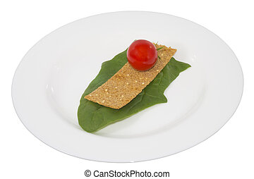 tomato on crouton and a leaf in a plate, it is isolated