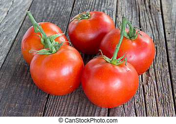 Tomato on old wooden background