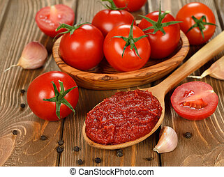 tomato paste in wooden spoon on brown background