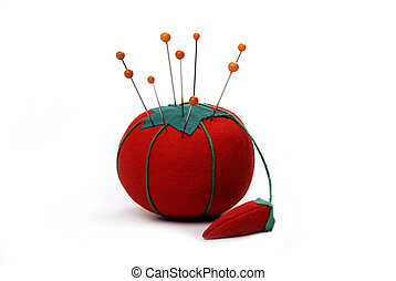 Orange pins stuck into a pin cushion in the shape of a tomato