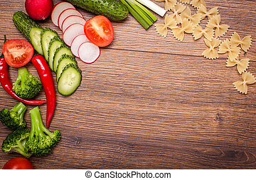 tomato, radish, cucumber, broccoli, onion, chili, pasta, macaroni on a wooden surface. arrangement of sliced vegetables. Top view with copy space for text