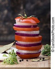 Tomato sandwich with onion on a wooden cutting board