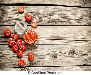 Tomato sauce in a glass jar with fresh tomatoes.