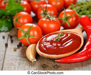 tomato sauce in a wooden spoon on brown table