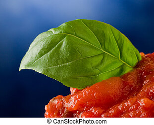 Tomato sauce with basil leaf background