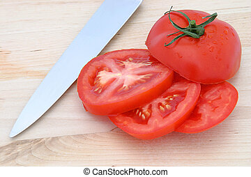 Tomato Slices & knif - A sliced tomato on a wooden cutting ...