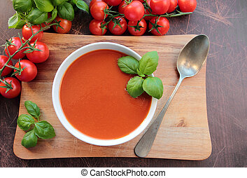 Tomato soup in a bowl on wooden board with spoon