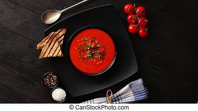 Tomato soup in black bowl with crisp bread - From above view...