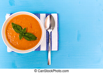 Tomato soup on wooden turquoise table. Top View, free space for text