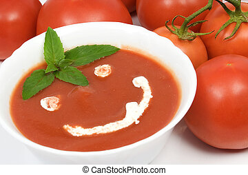 Tomato soup with basil leafs and sour cream as decoration