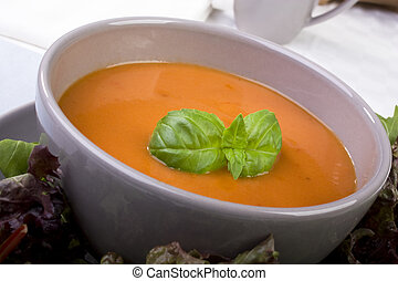 Enticing tomato soup with basil leaves as garnish. Great lunch for the dieter.