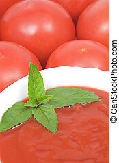Tomato soup with basil leafs and more tomatoes as background