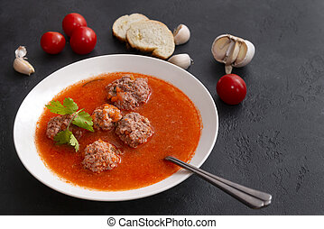tomato soup with meatballs on a black background