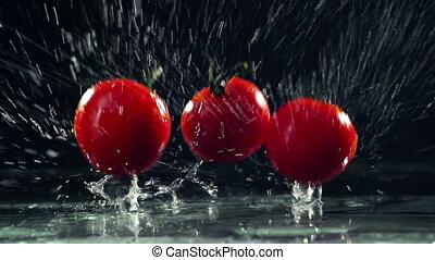 Tomato Splash - Dynamic shot of three tomatoes falling on...