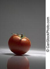 Tomato - Tomate fresco y rojo, reflejado sobre fondo negro.