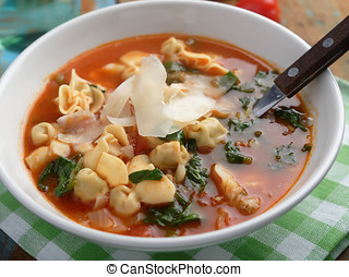 Tomato tortellini spinach soup with Parmesan cheese on a...