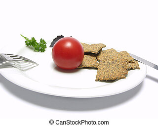 Tomato with hand make crisp bread on a white plate