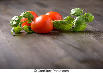 Tomatoes and basil on a wood table