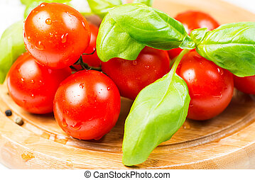 Tomatoes and basil on wooden cutting board