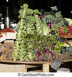 Tomatoes and Brussels sprouts in wooden boxes on the Borough market