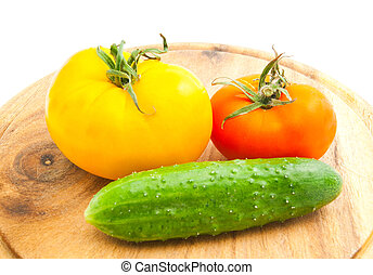 tomatoes and cucumber on wooden cutting board