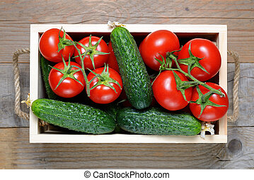 Tomatoes and cucumbers in wooden box close-up