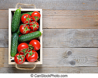 Tomatoes and cucumbers in wooden box top view