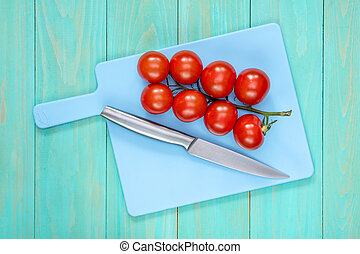 Tomatoes and knife on a blue cutting board