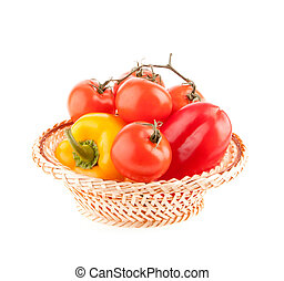 tomatoes and peppers in a wicker basket on a white background