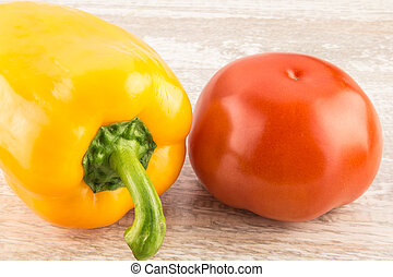 Tomatoes and yellow sweet peppers on a white wooden background close up.