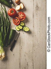 Tomatoes, cucumber, slices of vegetables with the black handle knife