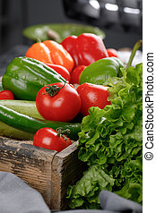 Tomatoes, cucumbers, greenery in a wooden tray.