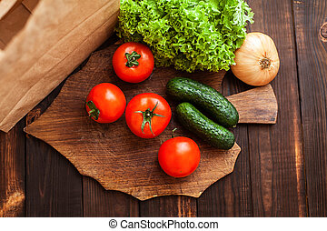 Tomatoes, cucumbers, lettuce, onions on a cutting board.
