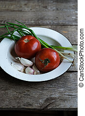 Tomatoes, garlic, and scallions on old wooden table.