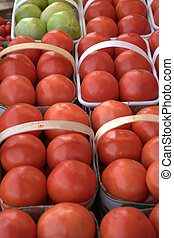 An array of ripe tomatoes in 6 quart baskets on a stand at a farmers' market